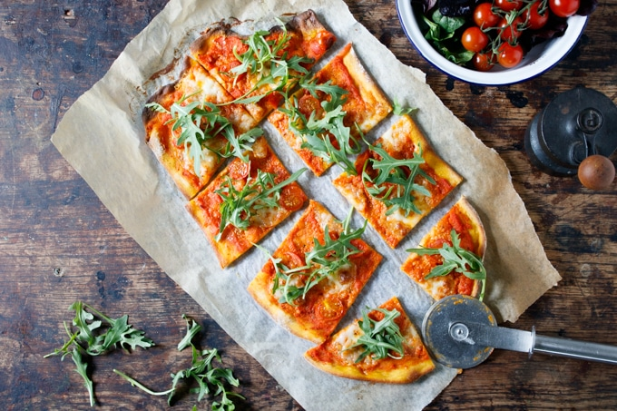 Carrot Pizza with Carrot Pizza Sauce being cut into slices.
