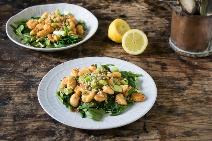 Two white plates piled with Sauteed Butter Bean Salad with Spinach (Lima Bean) and topped with toasted seeds and a squeeze of lemon juice.