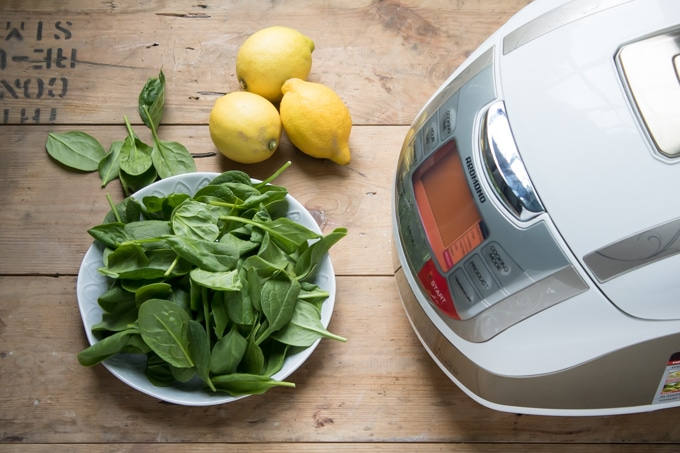 Multicooker on a table next to spinach and lemons.