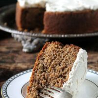 Carrot Peeling Cake with Cinnamon Icing, a slice on a vintage plate with the cake in the background