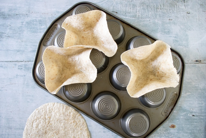 Tortillas being cooked between the cups of an upturned muffin tray to form bowls.