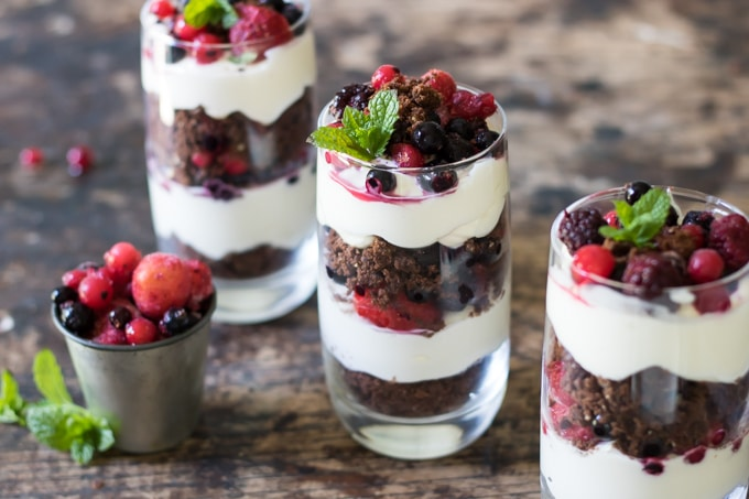 Cookie Cheesecake Parfait with Berries in glasses next to a pot of berries. The layered dessert is ready in minutes.