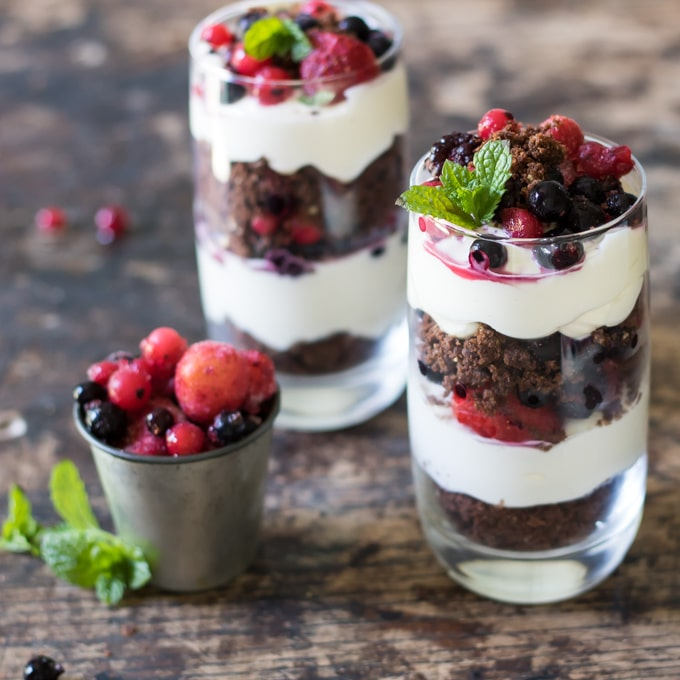 Glasses filled with layers of Cookie Cheesecake Parfait with Berries and topped with a sprig of mint.