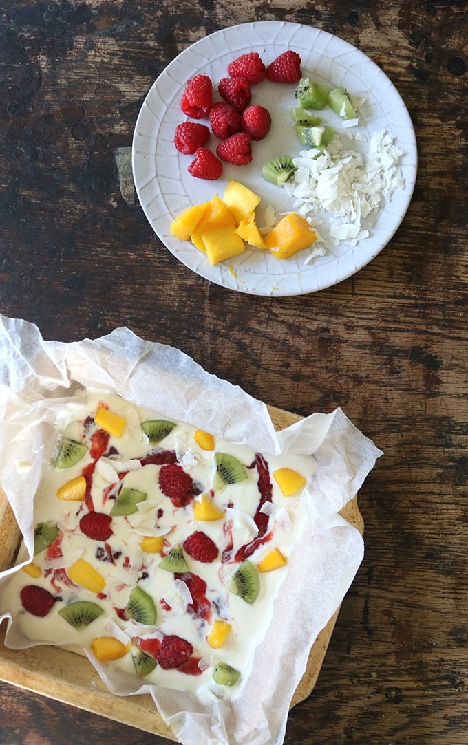 How to make Fruity Frozen Yogurt Bark - yogurt in a lined tray with swirls of strawberry jam and sprinkled with fruit and coconut, ready to be frozen.