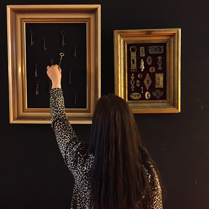 A person standing in front of frame with vintage keys.