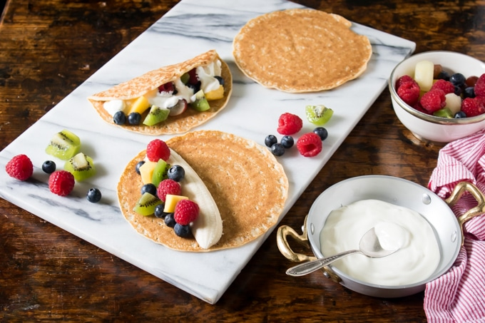 Fruit Tacos with Maple Yogurt being made on a marble tray. Crepes filled with bananas and fruit and topped with yogurt then folded.