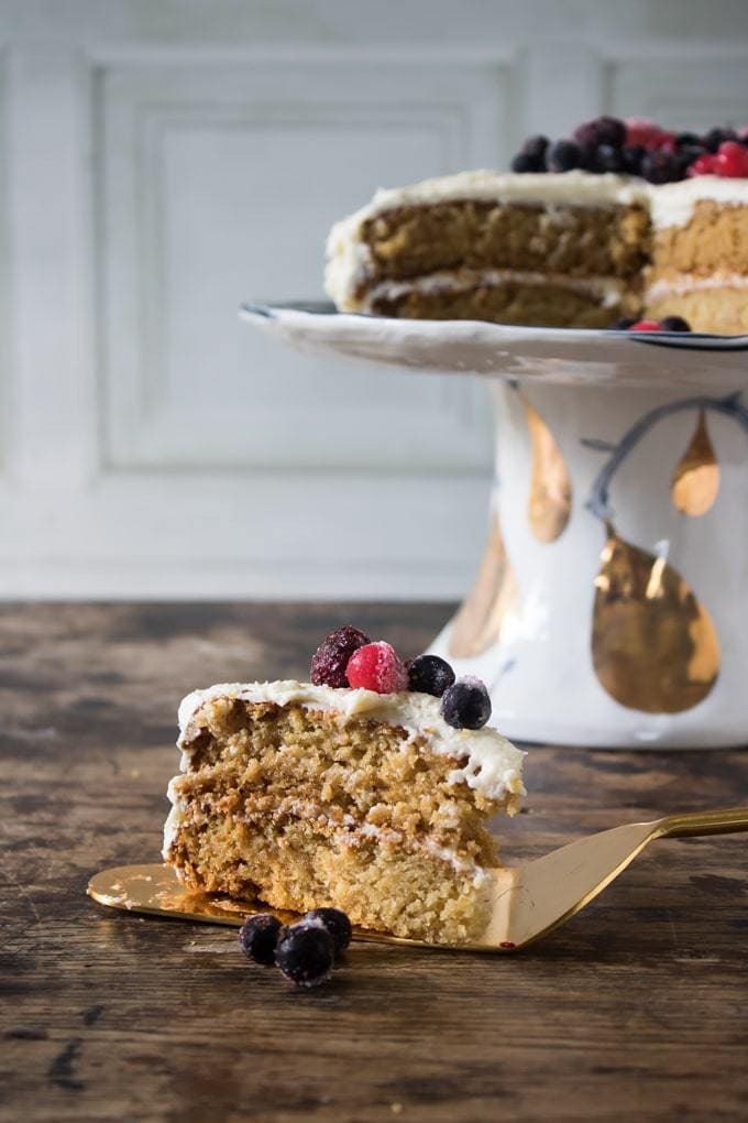 A slice of light and fluffy vegan vanilla cake topped with berries in front of the full vegan sponge cake