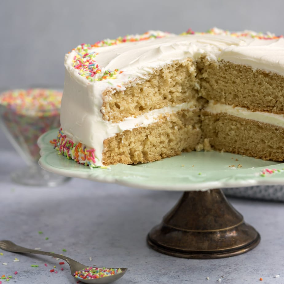 Vegan vanilla layer cake on a cake stand with slices removed.