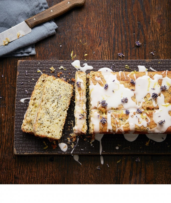 Loaf cake on a board next to a knife.
