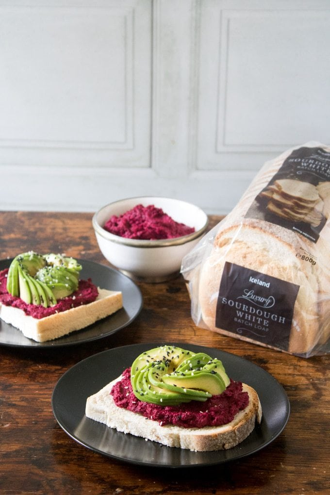 Beetroot Hummus on Toast with Avocado Rose next to a loaf of bread on a table.