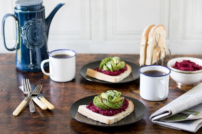 A breakfast table set up with coffee and toast topped with hummus and avocado.