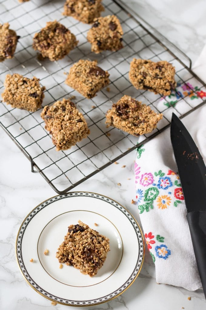A Chocolate Quinoa Bar on a plate and others on a cooling rack.