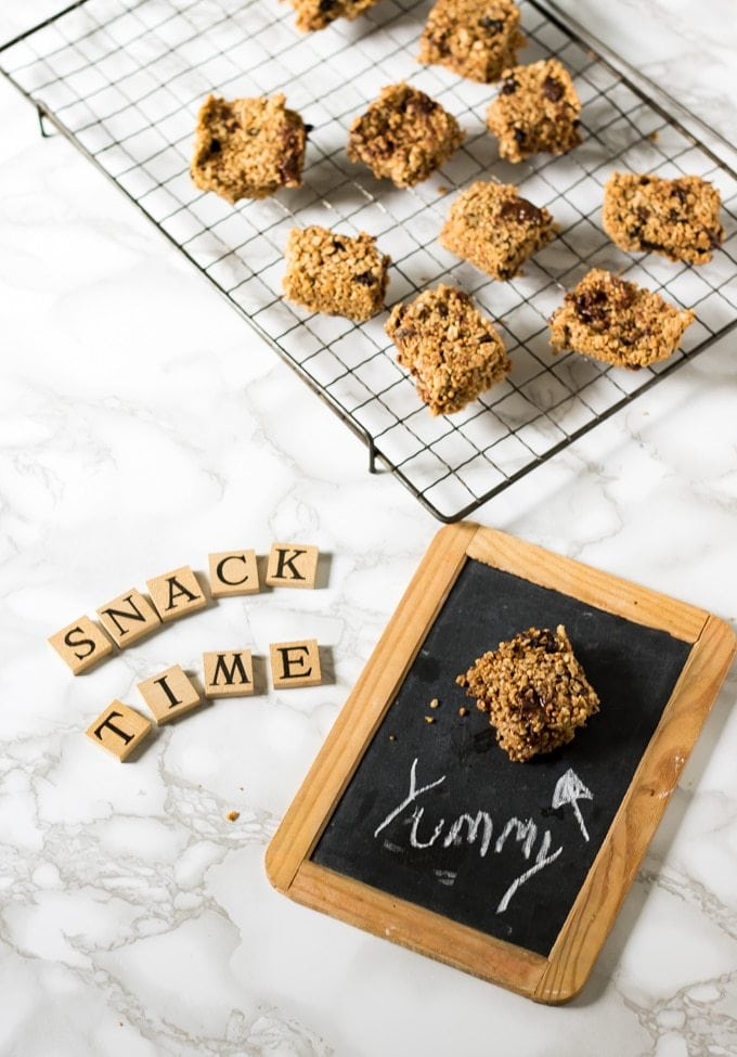 Chocolate Quinoa Bars with Oats and Raisins on a cooling rack, with Snack Time in letter tiles and an old fashioned slate with one bar on it and chalk writing says Yummy.