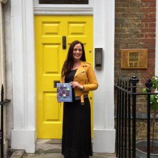 Kate Hackworthy in front of a publishing house door.