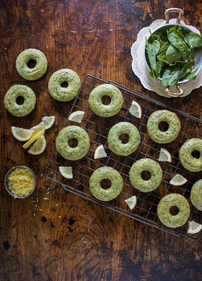 A table with Baked Lemon Spinach Doughnuts cooling. Ready to be drizzled with Lemon Glaze