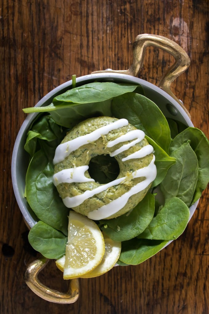 Donut on a plate of spinach leaves.