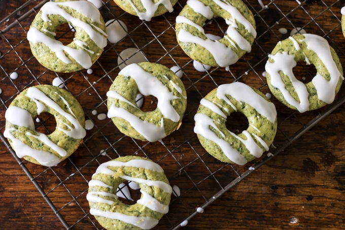 Spinach donuts with lemon drizzle on cooling rack.