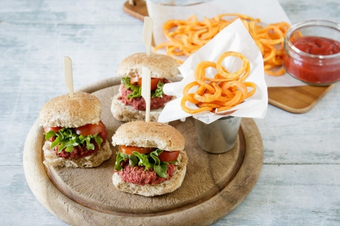 Easy Vegan Mini Beetroot Burgers on a wooden tray with sweet potato fries.