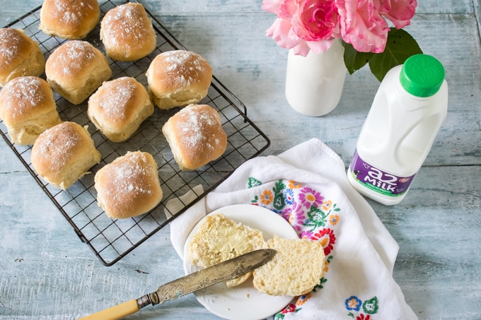 A rack of fluffy milk rolls cooling and spreading butter onto one warm roll. They're easy to make without much kneading.