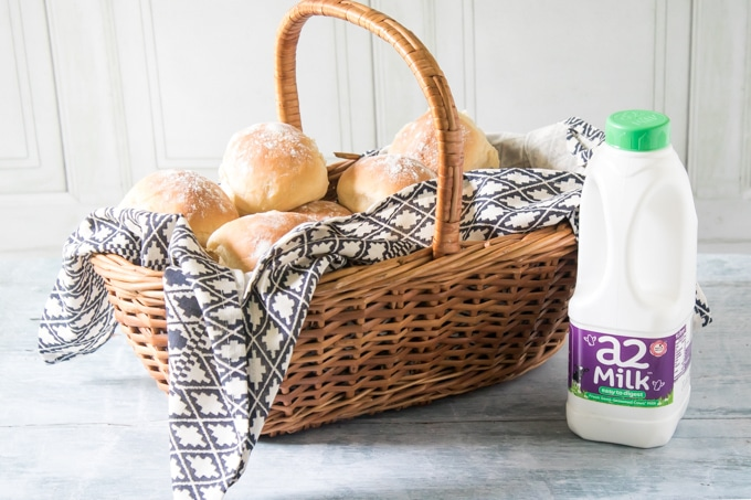 A basket of fluffy milk rolls and a bottle of a2 Milk which is easier to digest.