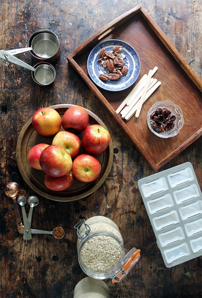 Ingredients shown for Apple Popsicles with Date Caramel Crumble. Pecans, dates, apples, oats, cinnamon