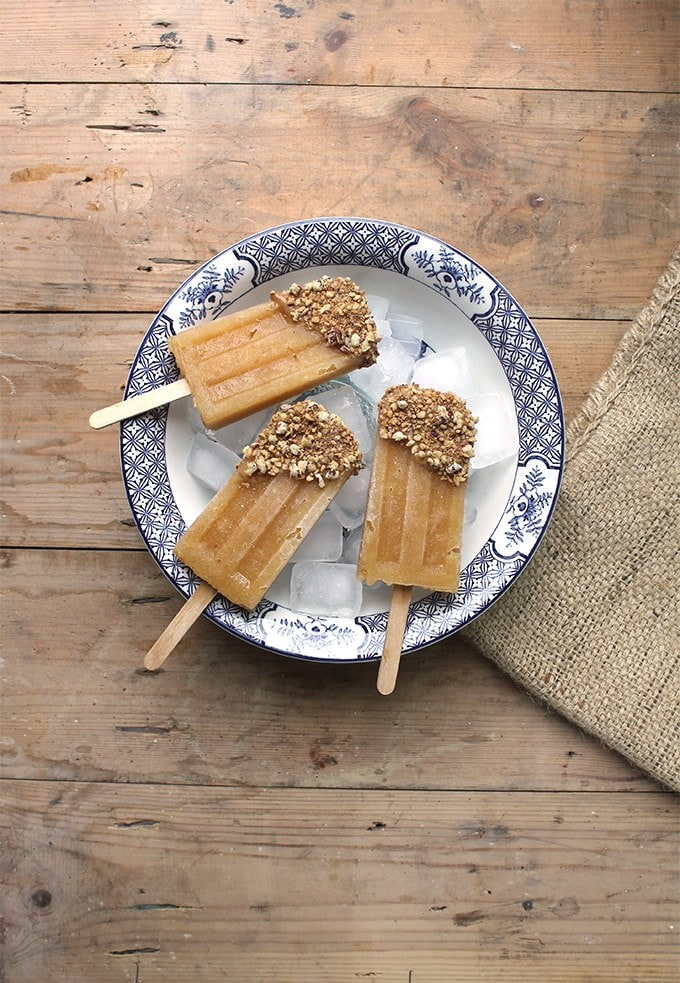 Apple Popsicles made with pureed cooked apples, topped with a little date caramel and chopped nuts. Three apple popsicles shown on a large bowl of ice.