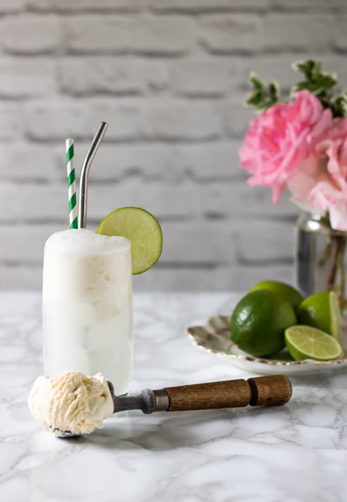Gin and Tonic Float in a glass with a scoop of vanilla ice cream and limes.