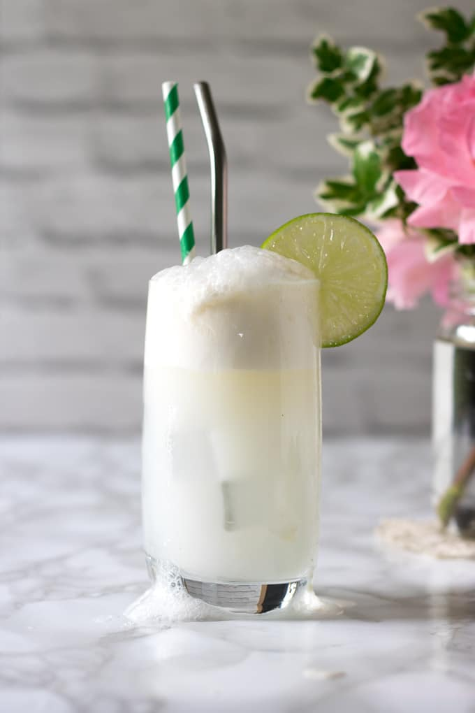 Gin and Tonic Float overflowing in a tall glass with straws and a slice of lime.