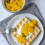 Mango compote made with fresh or frozen mango on a waffle on a white plate on a grey napkin next to a bowl of compote.