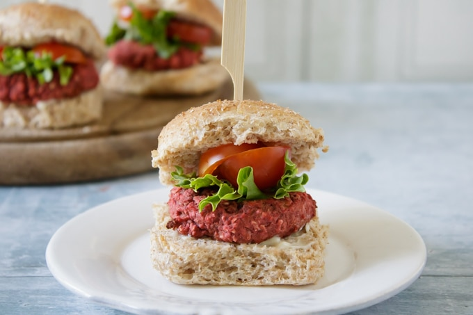Close up of an easy vegan Mini Beetroot Burger in a bun with lettuce and tomato