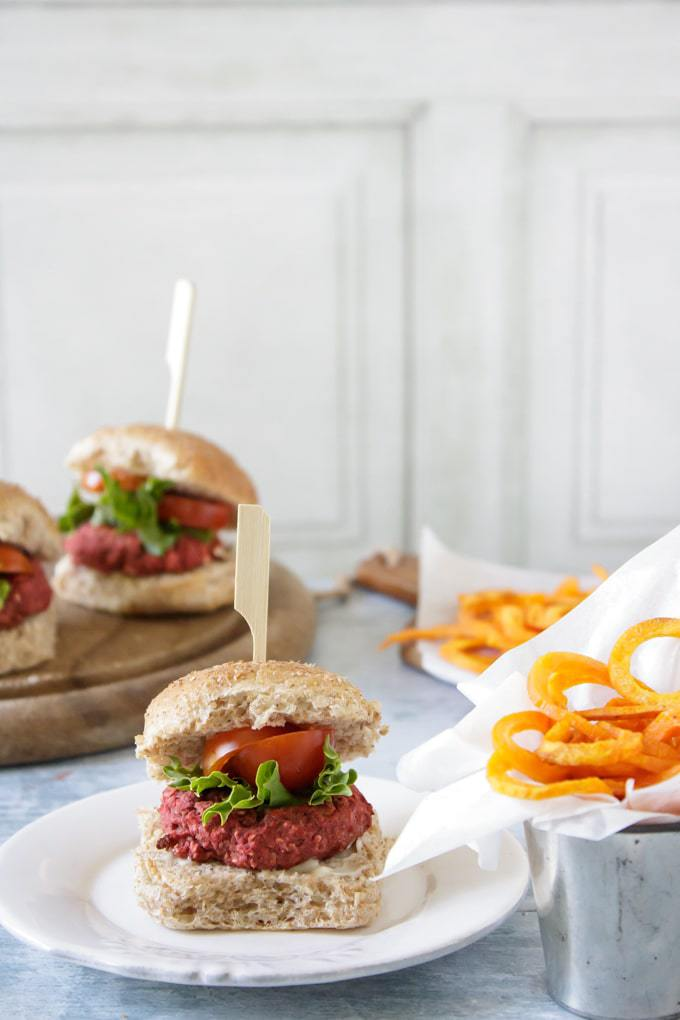 Mini beetroot burger in a bun with lettuce and tomato - on a plate next to a pot of spiralized sweet potato fries.