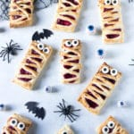 Make these quick and easy raspberry hand pies for halloween. They're a great way to get kids cooking. You can make the filling with fresh or frozen raspberries, or just use raspberry jam for a 3-ingredient halloween treat! Puff pastry rectangles spread with raspberry puree and strips of pastry on top to look like mummies.