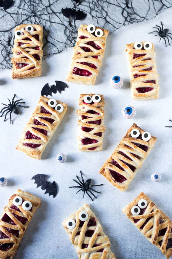 Pastry hand pies with raspberry filling and candy eyes. Strips of pastry on top to look like Halloween Mummys.