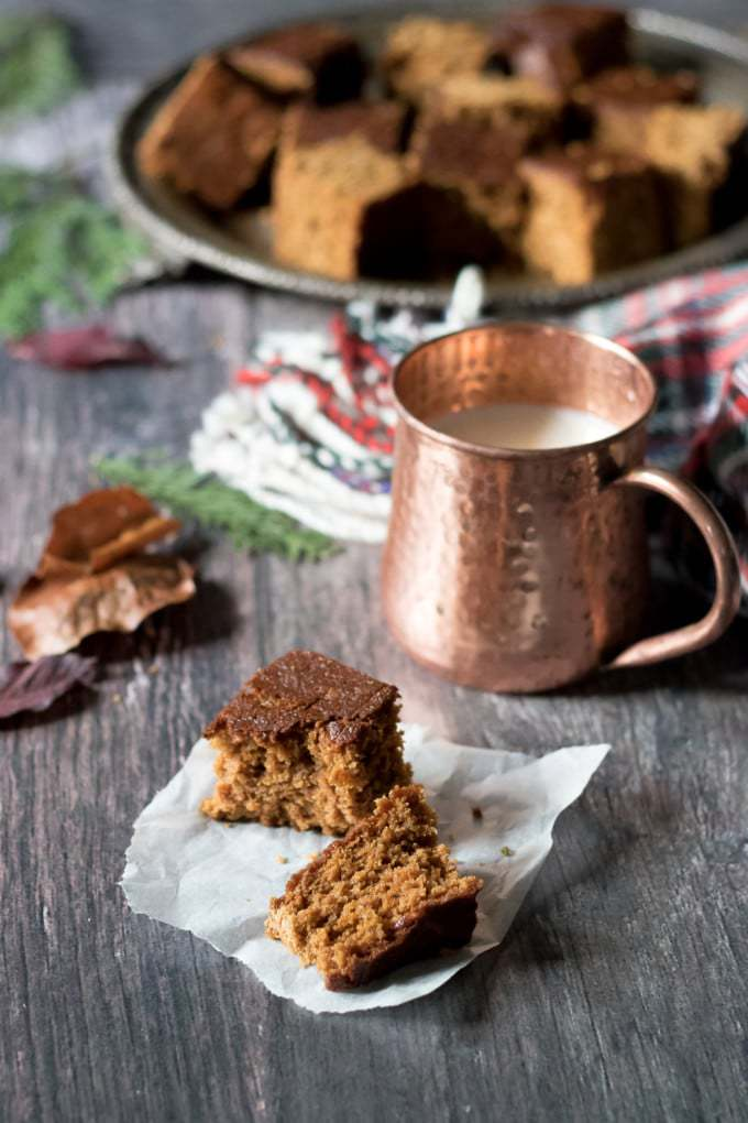 This sticky and spiced Parkin is a traditional ginger cake from Yorkshire shown on a piece of baking paper on a wooden table in front of a copper mug.