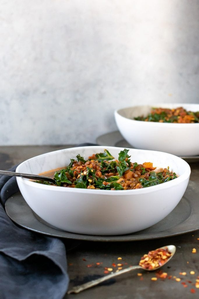 side view of a bowl filled with hearty Lentil Stew, with kale.