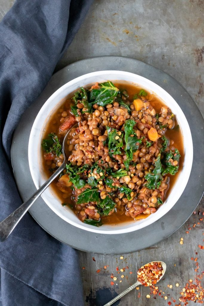a bowl of lentil stew with kale and harissa (spice paste), on a vintage plate with grey napkin