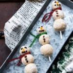Turn easy vegan no-bake almond coconut energy balls into Christmas snowman shapes by threading them onto sticks! Dried apricots and raisins are used for the noses and eyes.