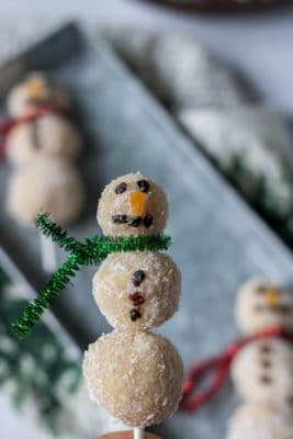 Coconut bliss balls threaded onto sticks and decorated to make fun snowmen
