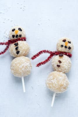 Coconut almond energy balls made into Christmas snowmen! These treats on sticks are easy and fun to make.
