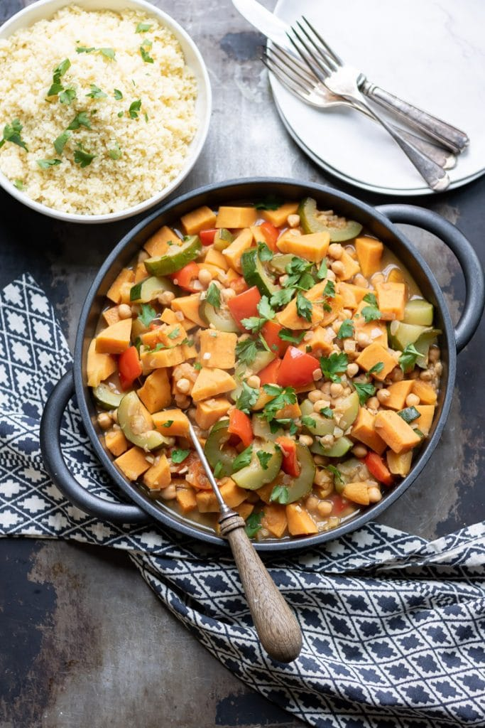 A cast iron dish of vegetable tagine with a bowl of couscous.
