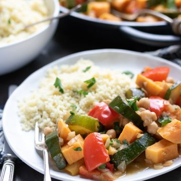 Close up of a plate of Moroccan Vegetable Tagine with couscous and a fork.