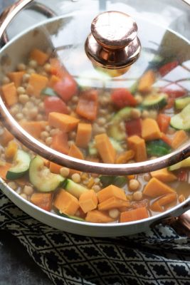 vegetables cooking in a pan with a lid