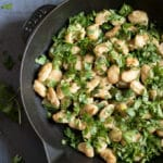 Herby Beans in a frying pan. A simple, easy and fresh side dish or soup topper.