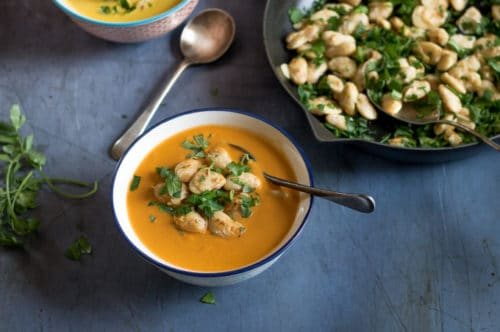 A bowl of tomato soup topped with pan fried white beans, with garlic and loads of fresh chopped herbs