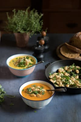 A bowl of tomato soup topped with pan fried white beans, with garlic and loads of fresh chopped herbs. Also makes a great gluten free and vegan side dish.