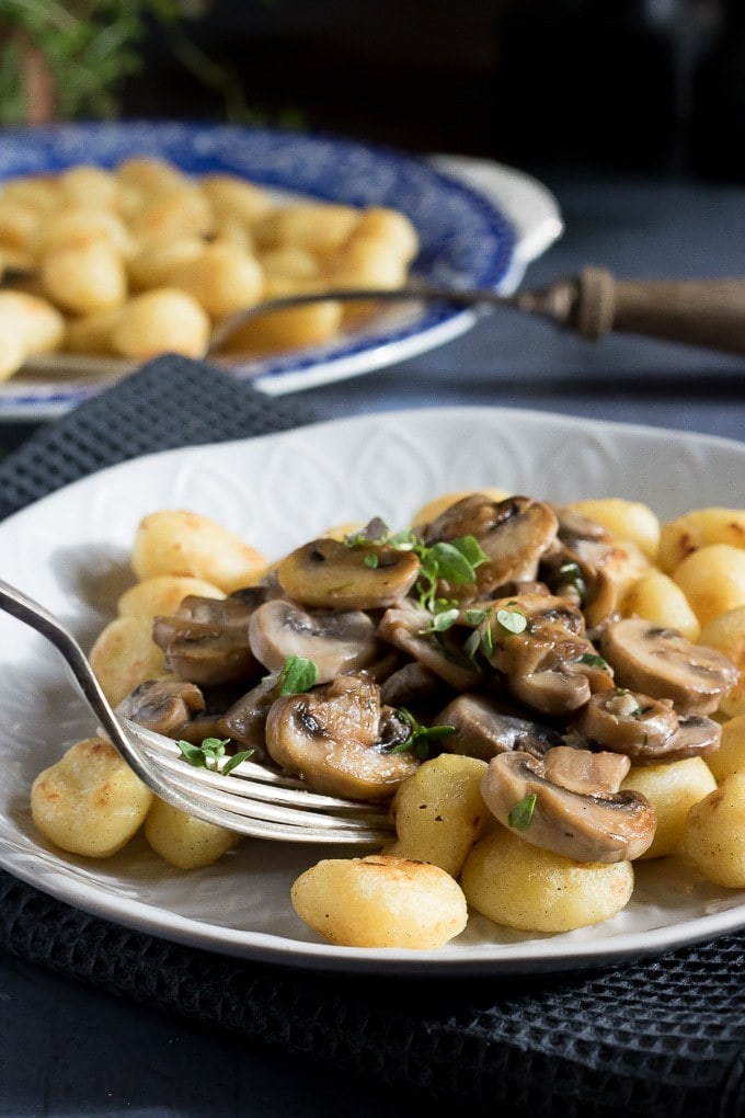 A plate of pan fried gnocchi topped with creamy garlic mushrooms and sprinkled with fresh thyme. A plate of fried gnocchi is in the background.