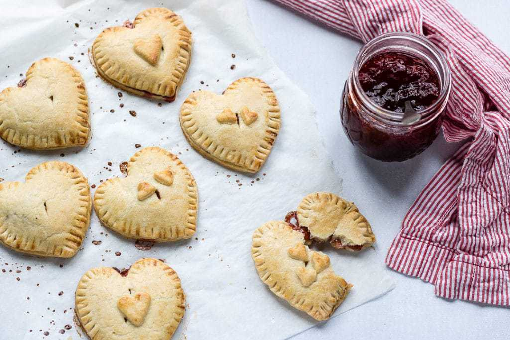 Overhead shot of heart-shaped easy jam hand pies with strawberry jam filling.