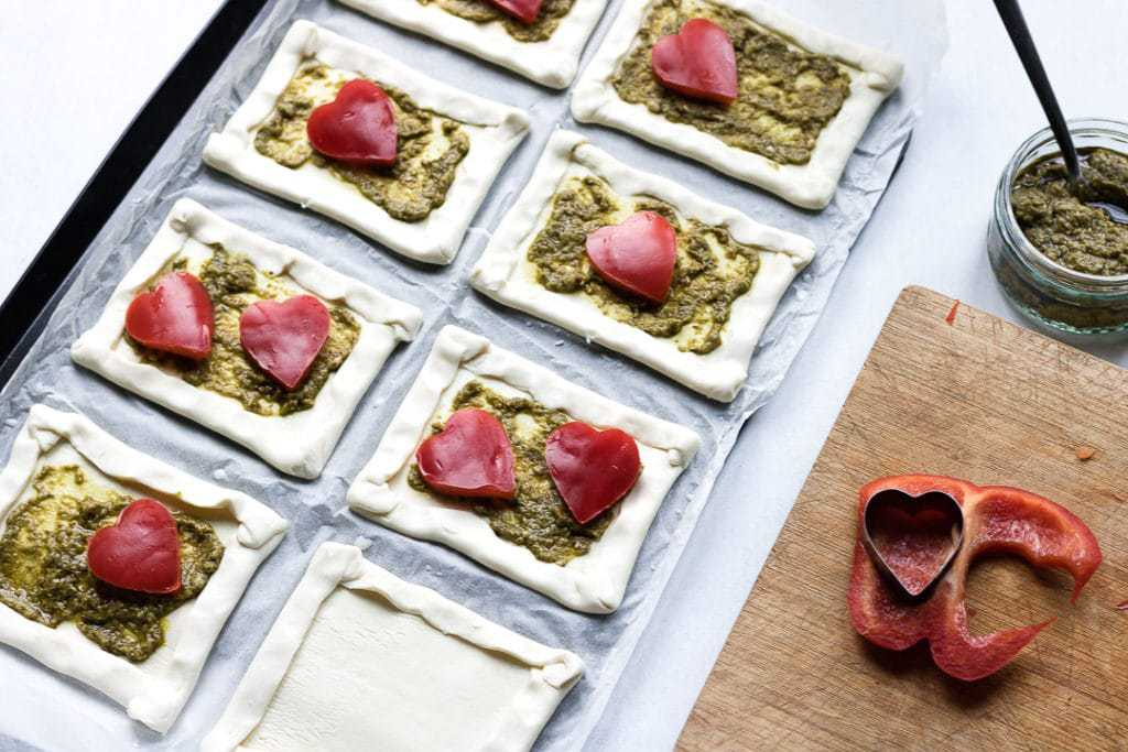 Step 2 to make puff pastry tarts: Pastry cut into squares, spread with pesto and topped with red peppers.