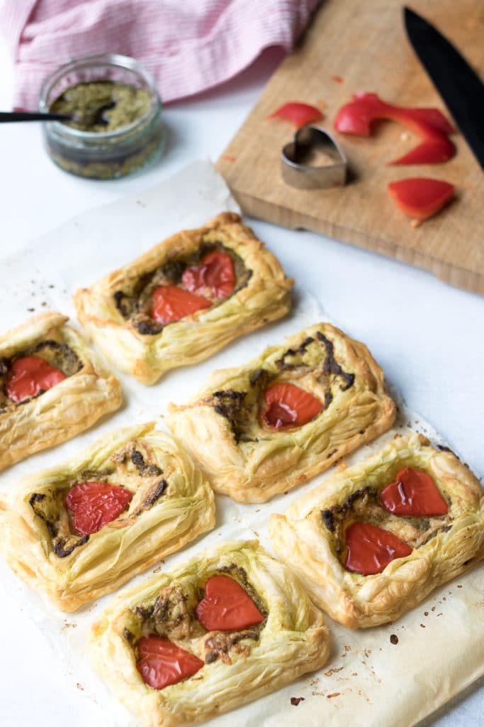 Cooked puff pastry tarts with pesto and red peppers cut into heart shapes with a cookie cutter for Valentine's Day. A quick and easy recipe that's perfect for cooking with kids.