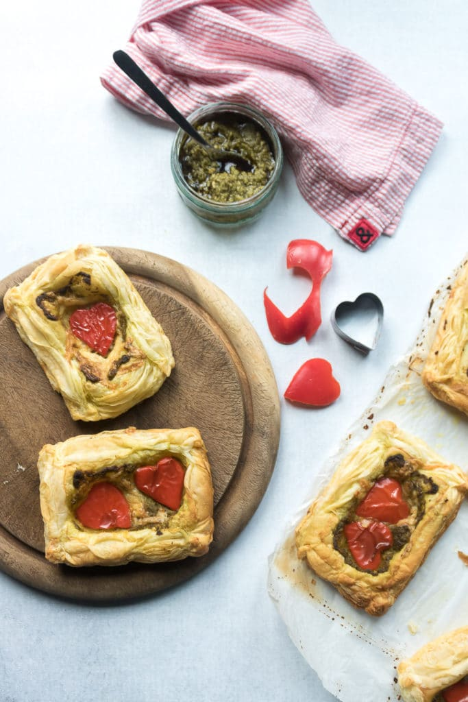 Easy 5 ingredient puff pastry tartlets on a bread board spread with pesto and red peppers cut into heart shapes with a cookie cutter for Valentine's Day.
